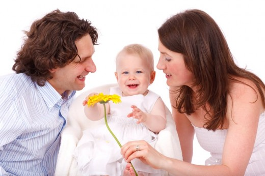 Man and Woman Holding Yellow Flower With Baby